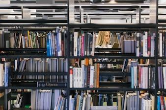 Hübscher Student in Bücherregalen