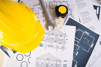Ingenieur Arbeitsplatz mit Blaupausen, Winkelmesser und Schutzhelm.