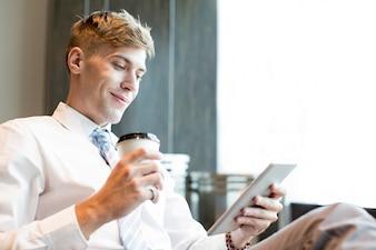 Inhalt Geschäftsmann mit Cup und Tablet