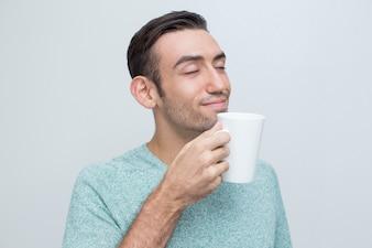 Inhalt Stattlicher junger Mann, der Tee vom Becher riecht