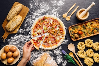 Italienische Lebensmitteldekoration mit Hand, die Pizza-Slce nimmt