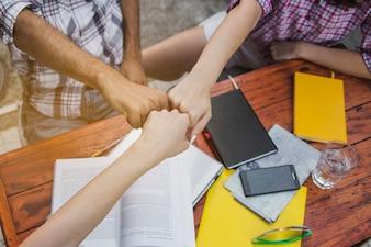 Jugendliche, die Hände mit Entschlossenheit stapeln