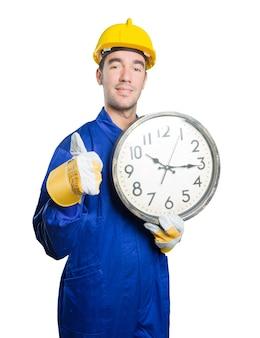 Junge Arbeiter besorgt über die Zeit auf weißem Hintergrund