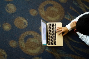 Junge auf dem Boden auf seinem Laptop arbeiten