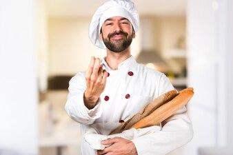 Junge Bäcker halten einige Brot kommende Geste in der Küche