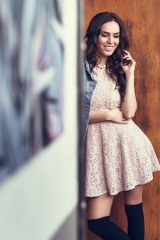 Junge brunette Frau lächelnd in städtischen Hintergrund.
