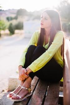 Junge Frau auf der Bank im Park