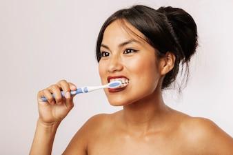 Junge Frau, die ihre Zähne putzt
