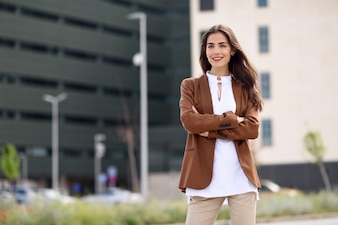 Junge Frau mit schönen Haaren stand außerhalb des Bürogebäudes.