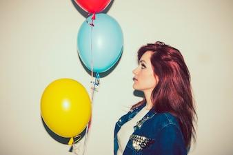 Junge Frau posiert seitwärts mit Ballons