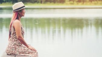 Junge Frau sitzt auf Pier und Blick auf den Fluss.