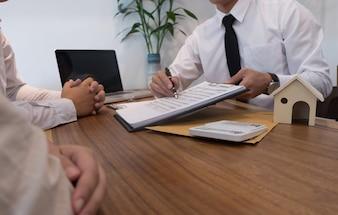 Junge Frau und Mann unterzeichnen Vertrag machen einen Deal mit Immobilienmakler.