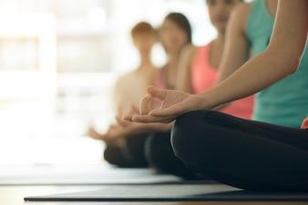 Junge Frauen Yoga drinnen bleiben ruhig und meditiert beim Üben Yoga, um den inneren Frieden zu erforschen. Yoga und Meditation haben gute Vorteile für die Gesundheit. Foto-Konzept für Yoga Sport und gesunde Lebensweise
