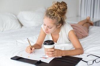Junge Geschäftsdame Arbeiten und Liegen auf Bett