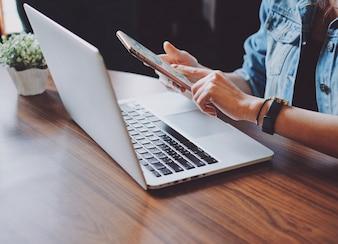 Junge Hipster Frau mit Smartphone und Laptop im Büro oder zu Hause