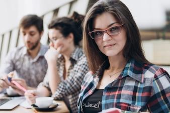 Junge intelligente Leute benutzen Gadgets beim Studieren in der modernen Bibliothek