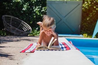Junge liest Buch liegend am Pool