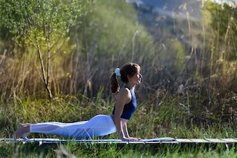Junge schöne Frau macht Yoga in der Natur