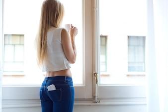 Junge schöne Frau zu Hause mit Handy in der hinteren Tasche.