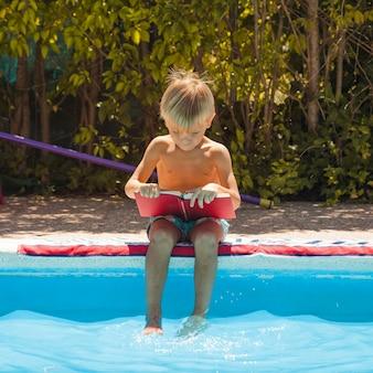 Junge sitzt am Pool mit Buch