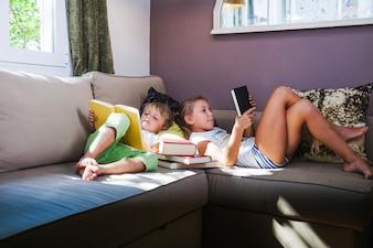 Junge und Mädchen mit Büchern im Sofa