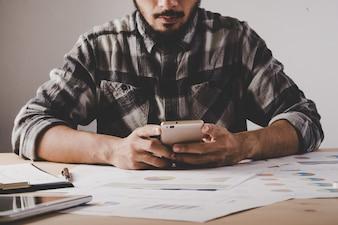 Junge Unternehmer sitzen und mit Handy am Arbeitsplatz im Büro. Business-Mann eine Pause machen während der Analyse Analyse mit Geschäftsdaten.