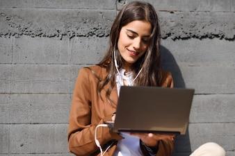 Junge Unternehmerin sitzt auf dem Boden Blick auf ihre Laptop-Computer. Schöne Frau trägt formale Abnutzung mit Kopfhörern.
