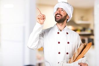 Junger Bäcker hält Brot und Denken in der Küche