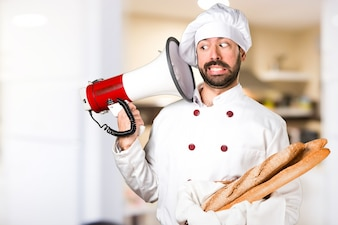 Junger Bäcker hält etwas Brot und schreit durch Megaphon in der Küche