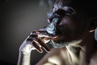 Junger erwachsener Mann, der im dunklen Raum raucht.