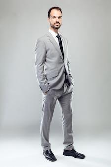 Junger Mann des Geschäfts, der Kamera über grauem Hintergrund betrachtet.