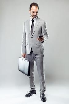 Junger Mann des Geschäfts, der sein Handy über grauem Hintergrund verwendet.