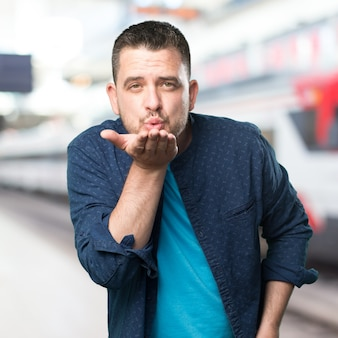 Junger Mann mit einem blauen Outfit tragen. Blasen einen Kuss.