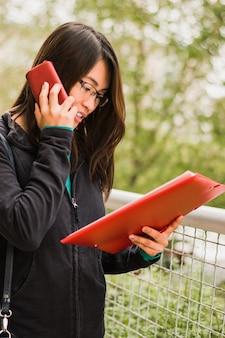 Junges Mädchen mit Smartphone einen Vertrag lesen