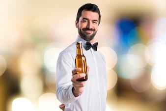 Kellner hält ein Bier auf unfokussierten Hintergrund