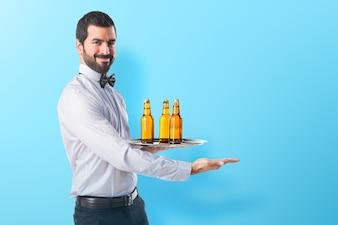 Kellner mit Bierflaschen auf dem Tablett, die etwas auf buntem Hintergrund präsentieren