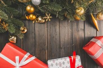 Kieferzweige mit Weihnachtsdekorationen auf Holzbrettern mit Geschenken unter