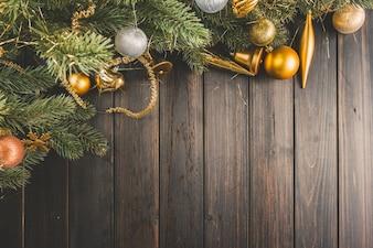 Kieferzweige mit Weihnachtskugeln auf Holzbrettern