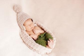 Kleine Baby in einer Wollmütze versteckt