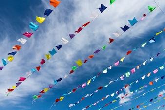 Kleine süße bunte Fahnen auf Seil hängen draußen für Urlaub mit hellen blauen Himmel weißen Wolken Hintergrund. Italien, Sardinien.