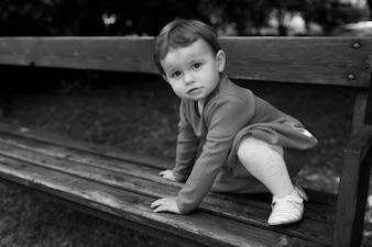 Kleine und süße Mädchen sitzt auf einer Holzbank