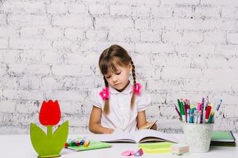 Kleines Mädchen am Tisch Hausaufgaben machen