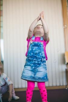 Kleines Mädchen in Rock fangen Blasen