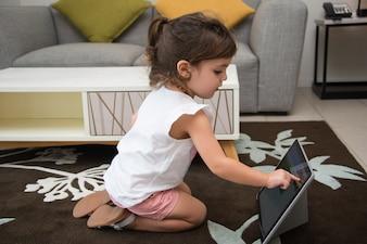 Kleines Mädchen mit Internet auf Tablette