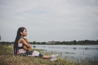 Kleines Mädchen sitzt mit ihrem Bären aufgeregt auf Wiesen Feld.