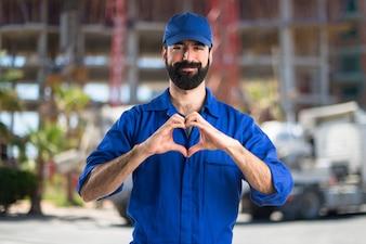 Klempner, der ein Herz mit seinen Händen auf unfocused Hintergrund macht