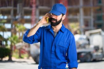 Klempner reden mit mobilen auf unfocused Hintergrund