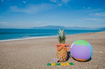 Komponierte Früchte und Ball am Strand