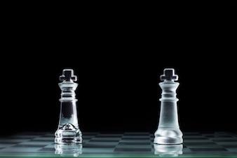 Konfrontation - zwei hölzerne Schachkönig, die gegeneinander auf einem Schachbrett stehen.