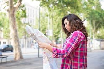 Konzentrierte junge Frau sucht auf der Landkarte